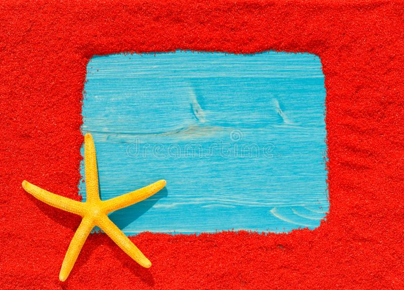 Colourful bright frame from red sand with a yellow starfish. Blue wooden empty card stock photography