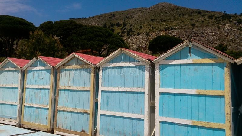 Colourful cabins on the beach with pines and mountains in the background royalty free stock images