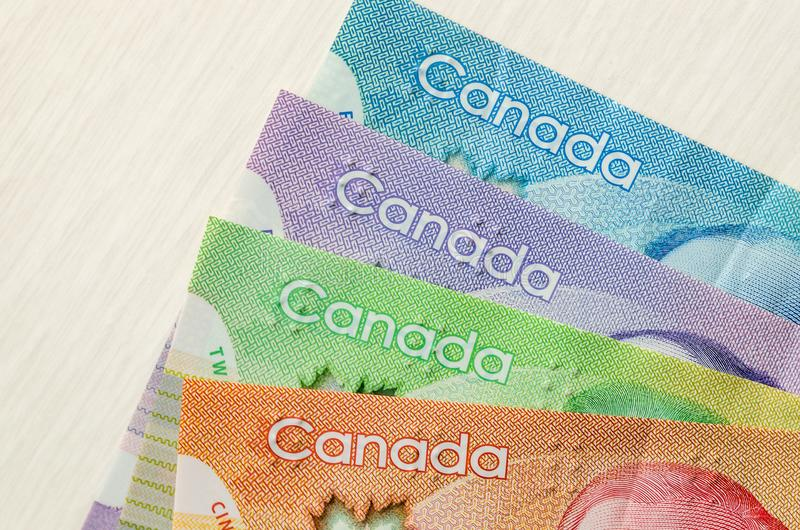 Colourful canadian dollar banknotes. On wooden background stock photo