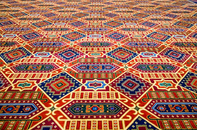 Colourful carpet, diminishing perspective. Colourful patterened carpet, focus on foreground with diminishing perspective royalty free stock images