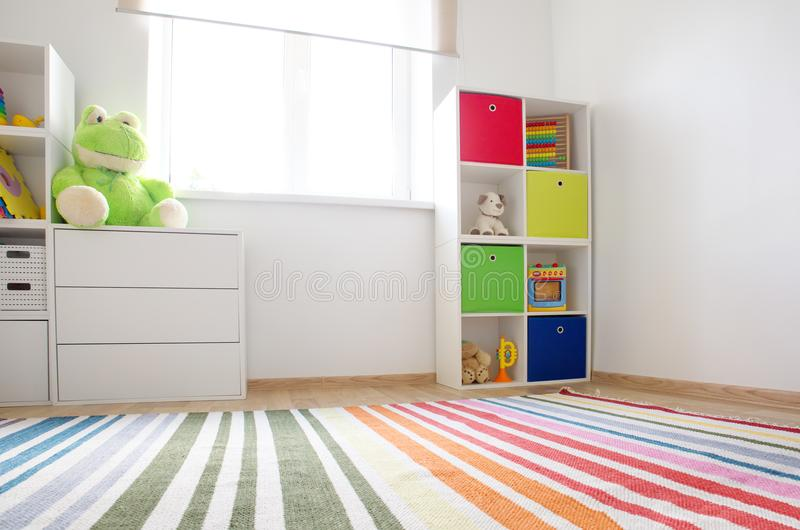 Colourful children rooom with white walls and furniture. Rainbow carpet at home interior with a window royalty free stock images