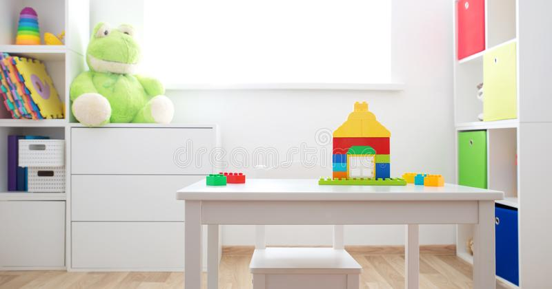Colourful children rooom with white walls and furniture. Rainbow carpet at home interior with a window stock image