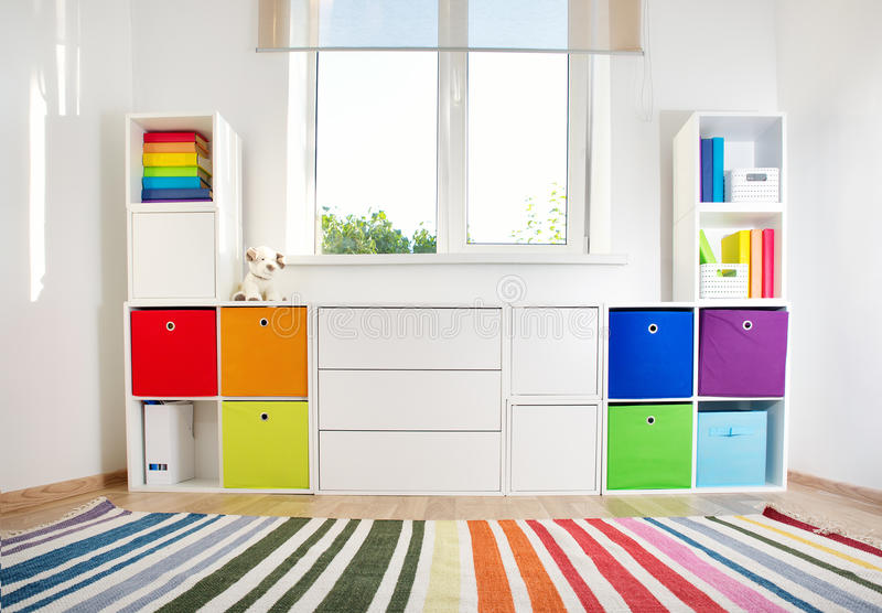 Colourful children rooom with white walls and furniture. Rainbow carpet at home interior with a window stock images