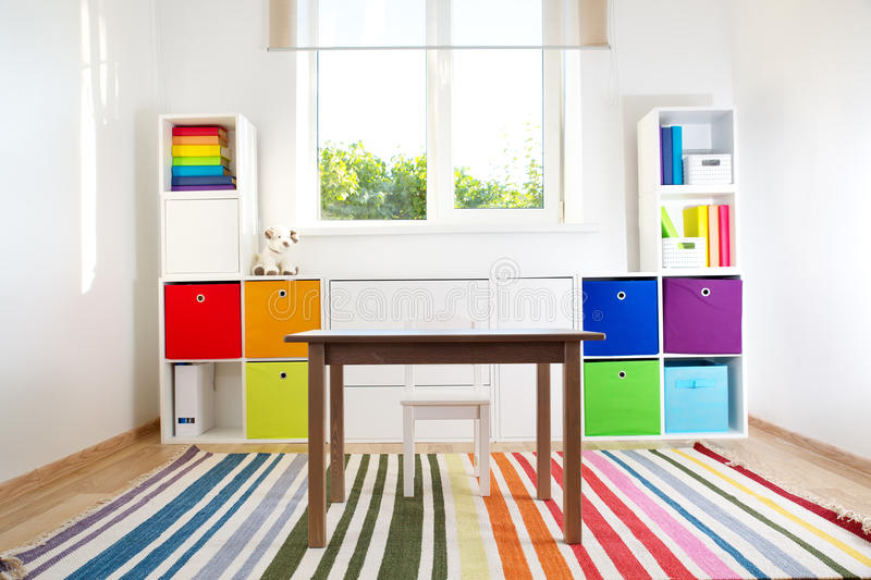 Colourful children rooom with white walls and furniture. Rainbow carpet at home interior with a window stock photography