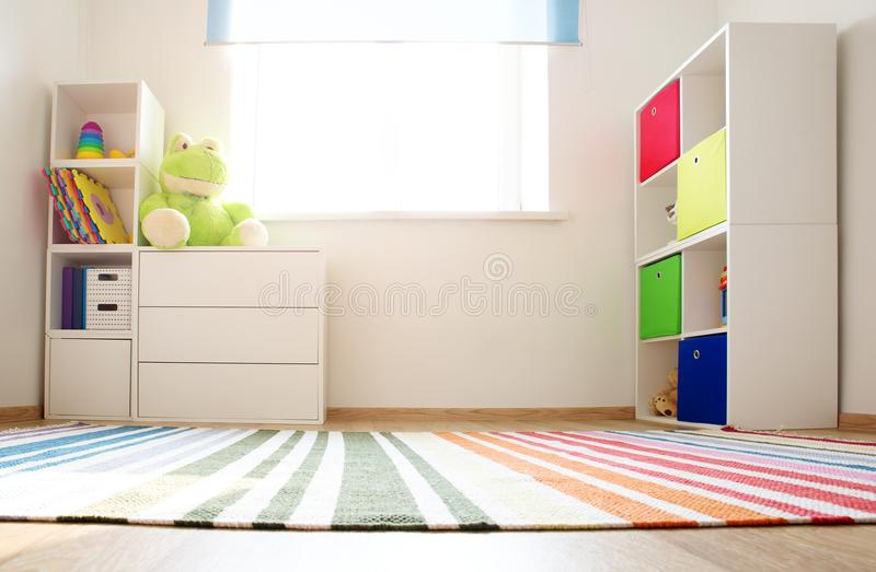 Colourful children rooom with white walls and furniture. Rainbow carpet at home interior with a window royalty free stock photography