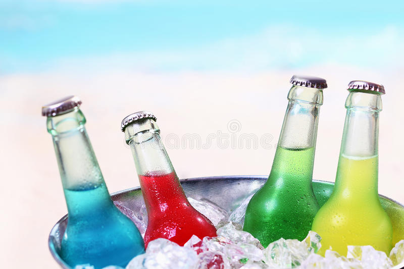 Colourful chilled soda drinks. In unlabeled glass bottles standing in a metal container of crushed ice cubes for a summer party stock photos