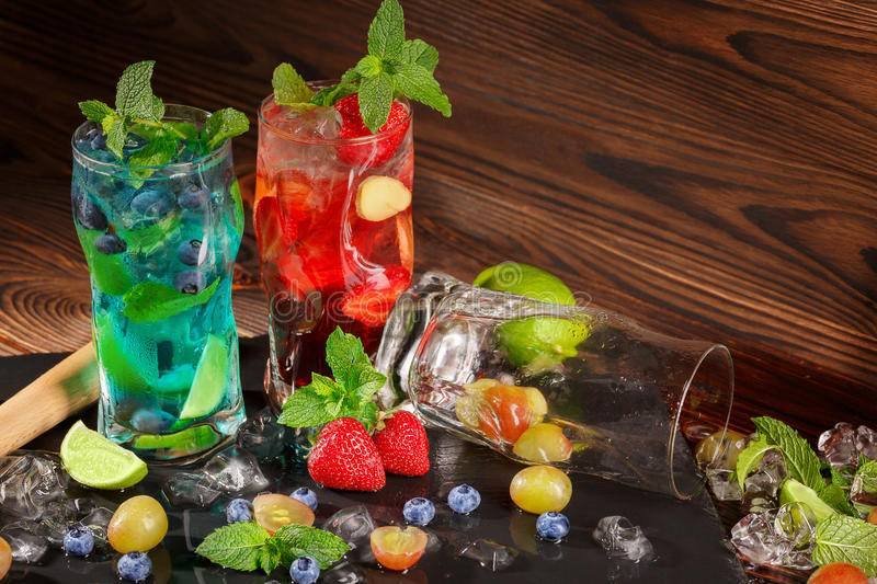 Colourful cocktails with mint, lime, ice, berries on the wooden background. Refreshing summer beverages. Copy space. royalty free stock photography