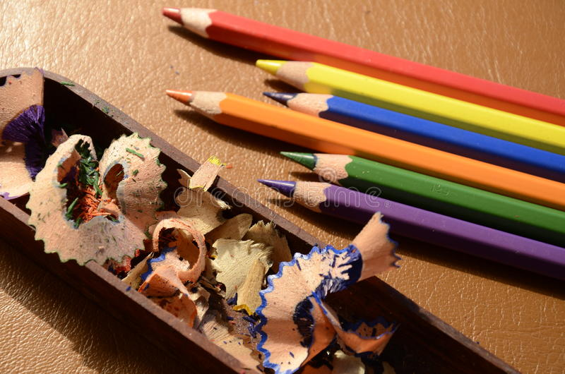 Colourful crayons. Sharpened with pencil sharpener lying on the leather background stock photography