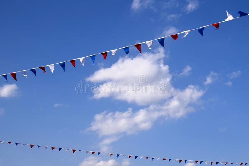 Colourful decorative triangular flags under blue sky with clouds stock image