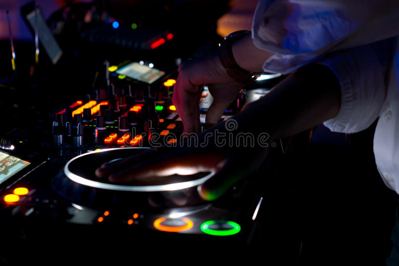 Colourful DJ music deck at night. With all the controls illuminated and the hand of the disc jockey suspended above the vinyl record on the turntable to mix and royalty free stock photos