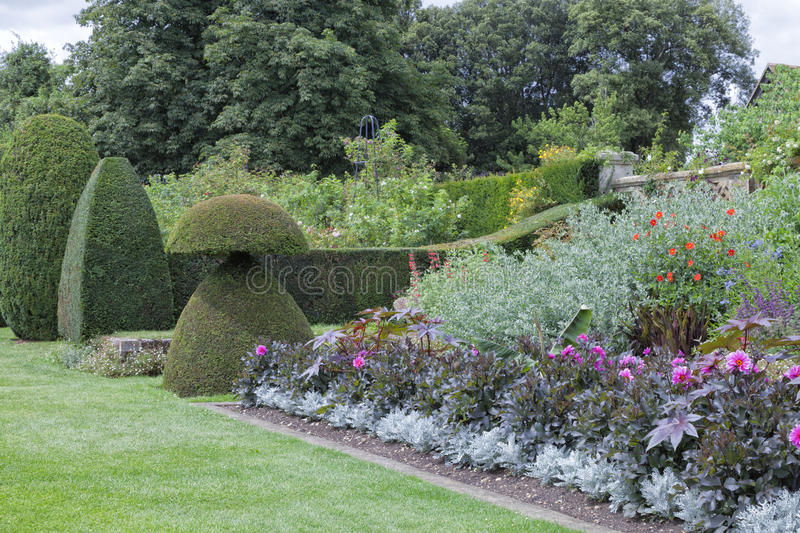 Colourful english garden with flowers, topiary plants, trees, shrubs royalty free stock photo