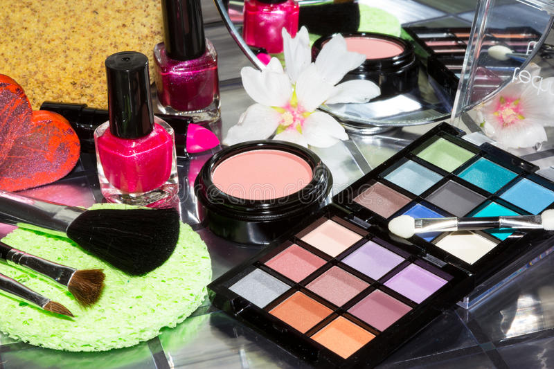 Colourful eye makeup with assorted cosmetics. Two open compacts of colourful eye makeup on a table with assorted cosmetics including blusher, nail varnish and royalty free stock photography