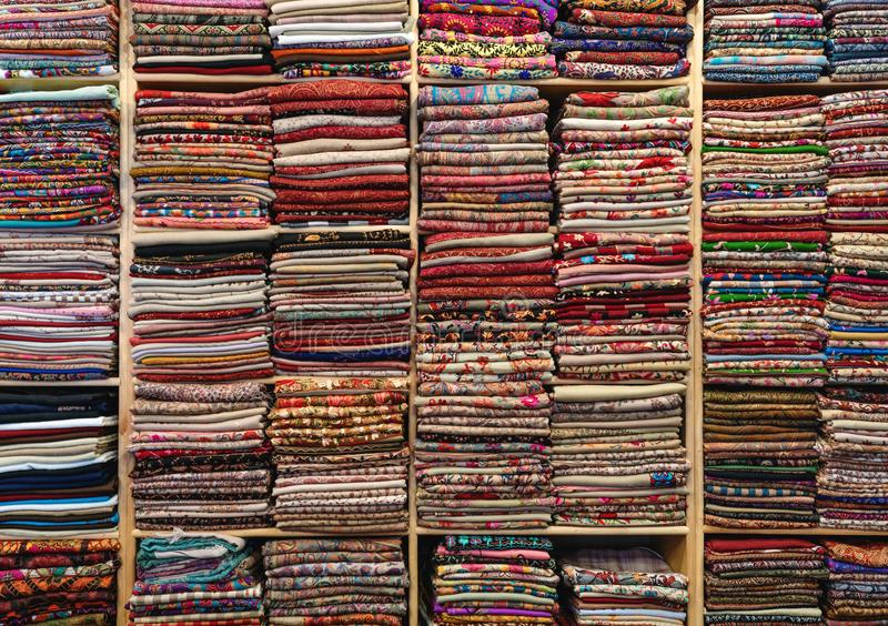 Colourful fabric, textile and silk on wooden shelf in fabric store royalty free stock image