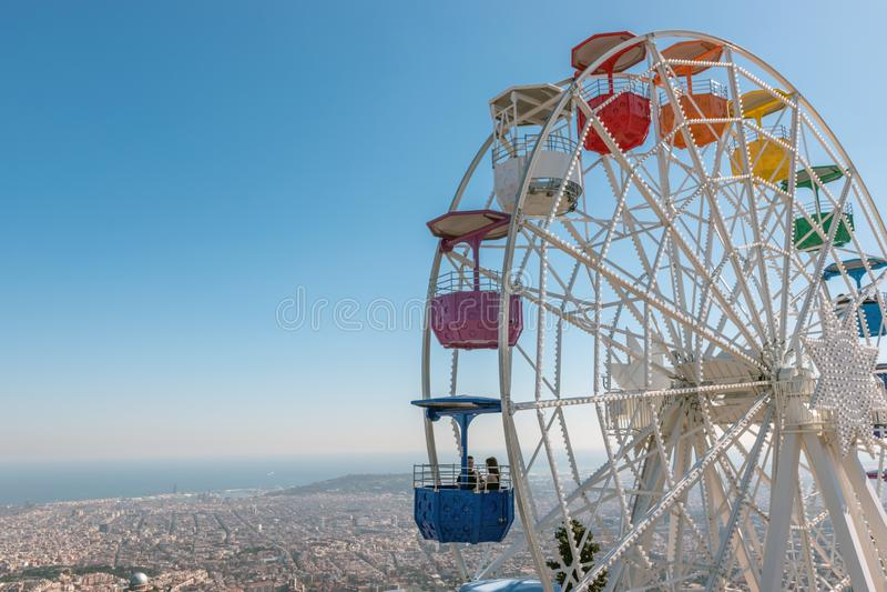 Colourful ferris wheel in the amusement park Tibidabo on background of blue sky, Barcelona, Spain stock photo