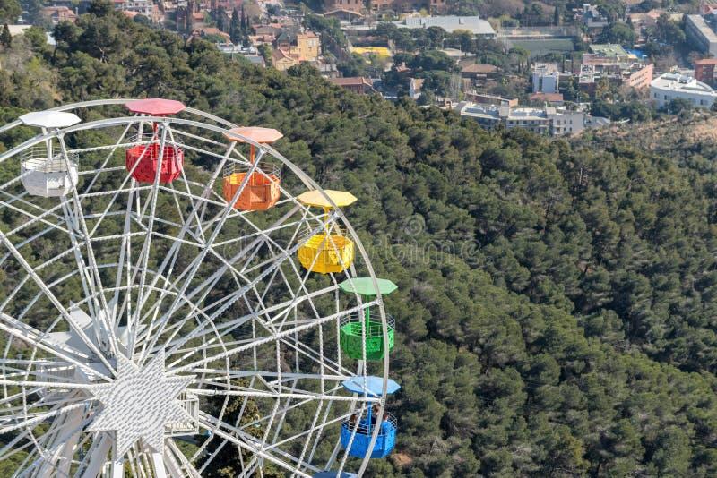 Colourful ferris wheel in the amusement park Tibidabo on background of blue sky, Barcelona, Spain.  stock photos