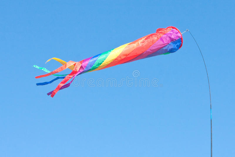 Colourful flag. A colorful toy flag or windsock blowing on a sunny summer day royalty free stock photo