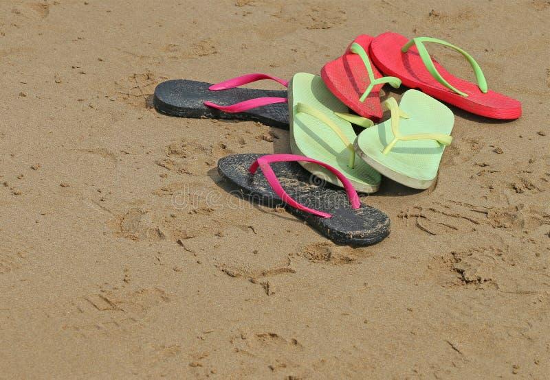 Colourful flip flop thongs on a sandy beach. Colourful red, green, pink and black flip flop thongs on a sandy beach stock photos