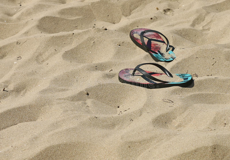 Colourful flip flop thongs on a sandy beach. In summer stock photography