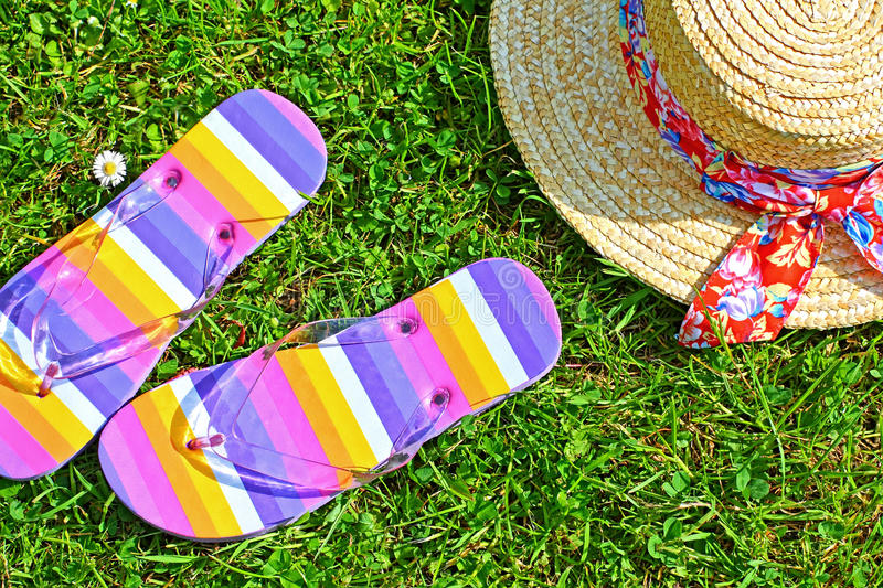 Colourful flip flops and a straw hat stock photography