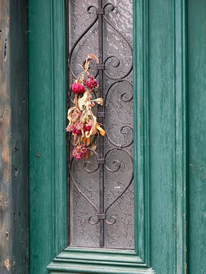 Colourful Flower Arrangement on Green Door, Galaxidi, Greece. A colourful dried flower bouquet hanging on a green front door, Galaxidi, Gulf of Corinth, Greece stock images