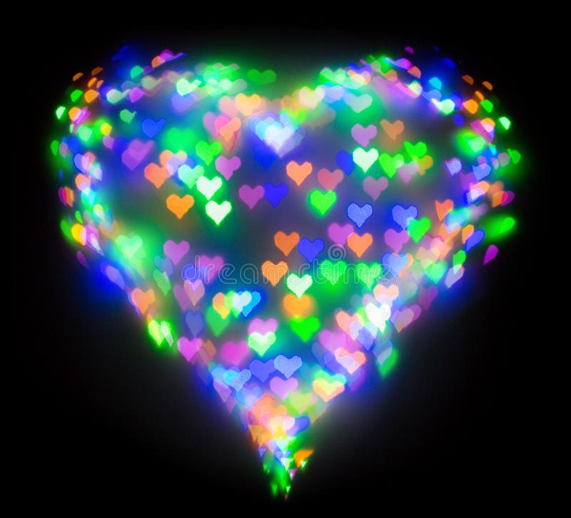 Colourful glitter formed a heart, bokeh in a shape of a heart. Festive background with de-focused colourful glitter formed a heart, bokeh in a shape of a heart royalty free stock photo