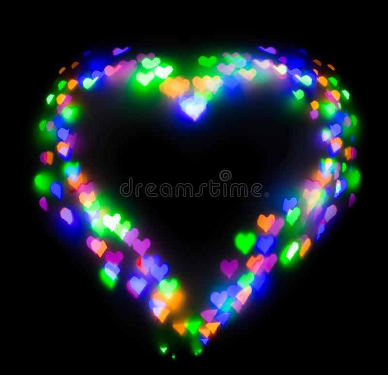 Colourful glitter formed a heart, bokeh in a shape of a heart. Festive background with de-focused colourful glitter formed a heart, bokeh in a shape of a heart stock photos