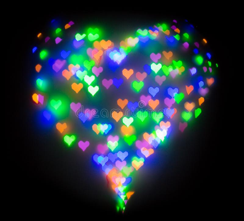 Colourful glitter formed a heart, bokeh in a shape of a heart. Festive background with de-focused colourful glitter formed a heart, bokeh in a shape of a heart stock photography