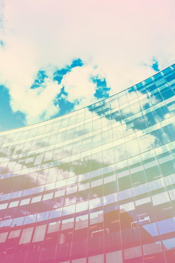 Colourful, graphic image of glass skyscraper, modern background. Colourful, graphic image of glass skyscraper and blue sky in modern background royalty free stock photo