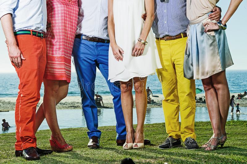 Colourful group of friends standing at the beach stock image