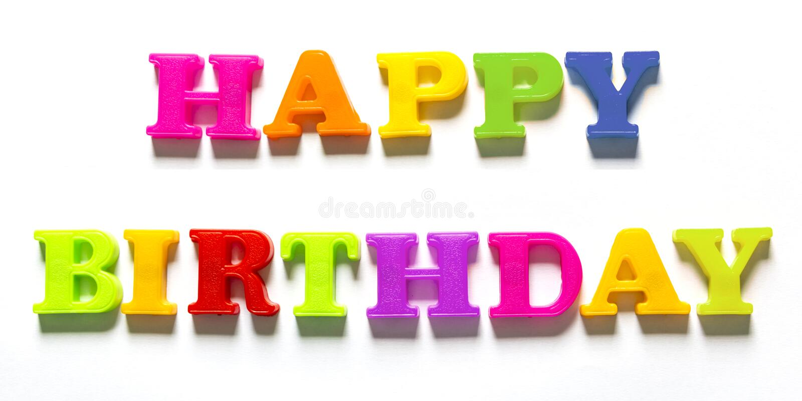 Colourful Happy Birthday Capital Letters in White Background. Image of happy birthday words made from colourful plastic letter magnets isolated in white royalty free stock photo