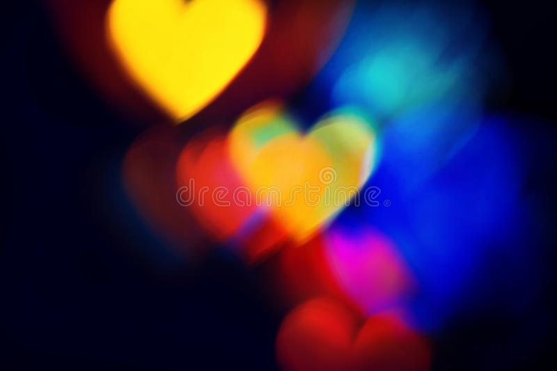 Colourful heart bokeh background. Blurred Colourful heart shapes bokeh sparce on dark background. For Christmas and Valentine`s day greeting cards, invitations stock photo