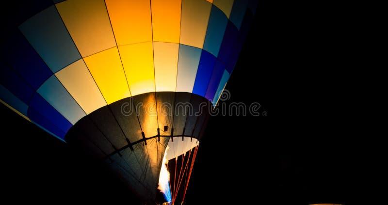 Hot air balloon at night. Colourful hot air balloon filling up at night royalty free stock photos