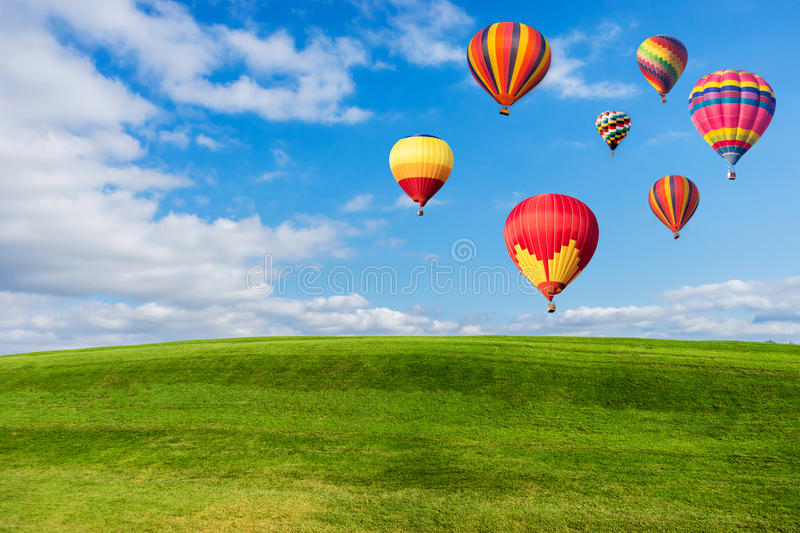 Colourful hot air balloons flying over green field. And blue sky stock image