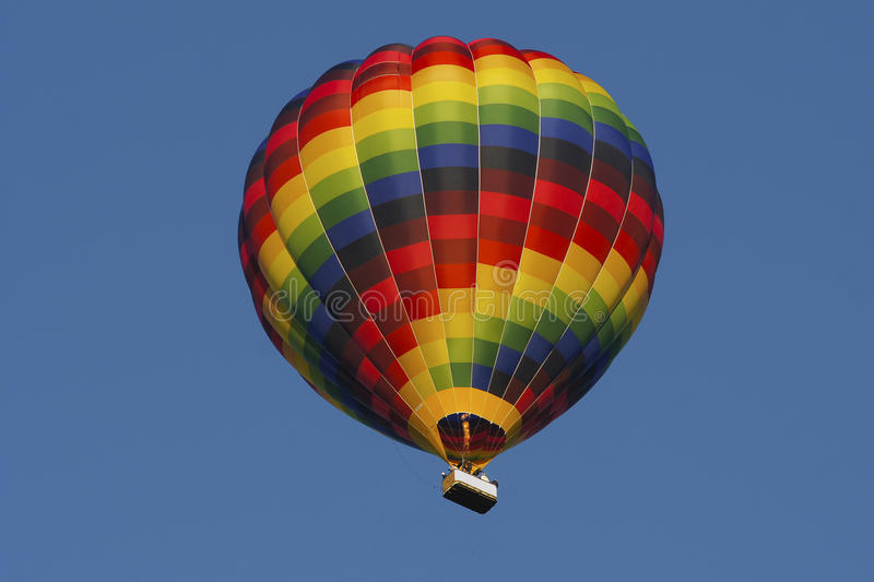 Colourful hotair balloon with clear blue sky. Hot air balloon against clear blue sky. The balloon is red, blue, green and yellow with colors in spiral shape stock photo
