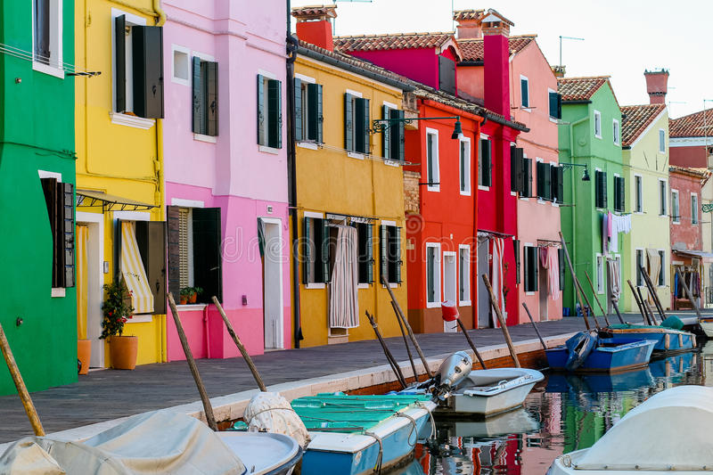 Colourful italian houses. Italian colorful houses are on the channel. Boats of fishermen approached near the shore royalty free stock image