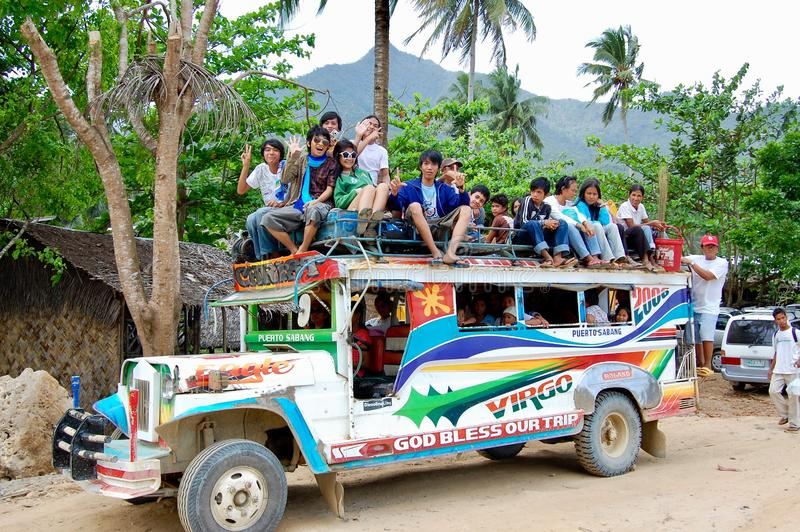 A colourful Jeepney taxi full of people on the roof prepares to leave the rural village stock photo