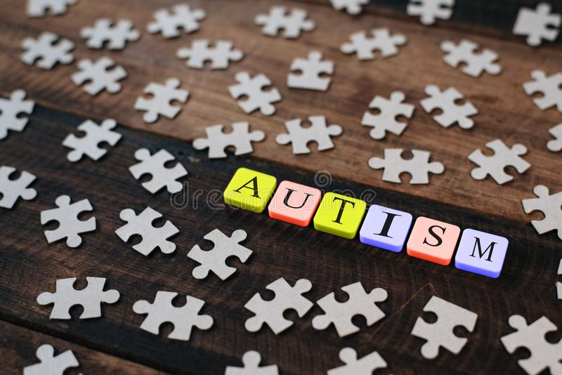 Colourful jigsaw puzzle and alphabet tiles with AUTISM word on wooden table stock photo
