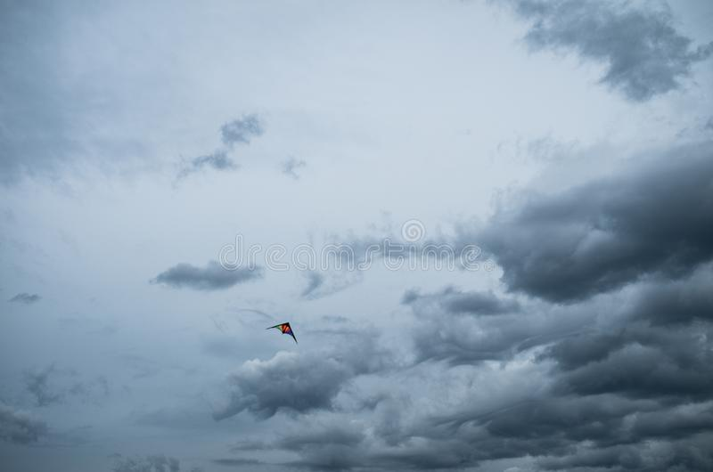Colourful kite flying in a cloudy stormy sky. royalty free stock photography