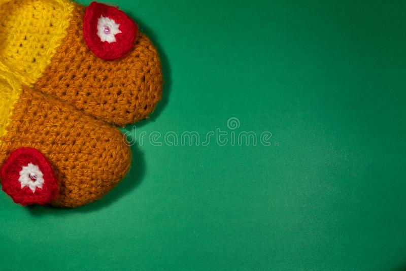 Colourful knitted Slippers on a green background. Colorful knitted baby Slippers with a red flower on a green background royalty free stock photo