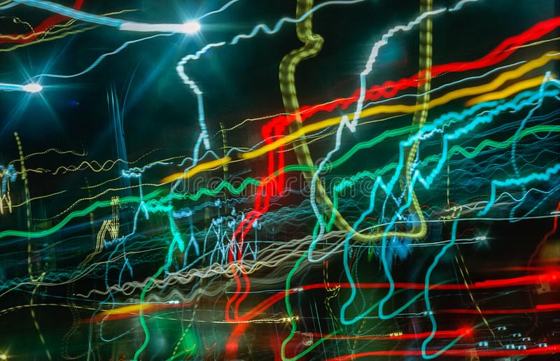 Colourful light streaks from street signs and passing cars at night. Frenetic looking long exposure colourful light streaks from street signs and passing cars stock images