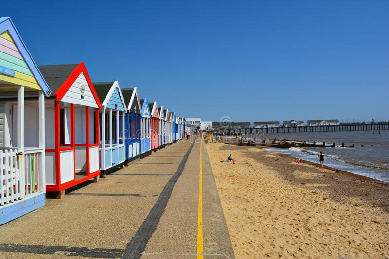 Colourful line of beach huts and pier royalty free stock image