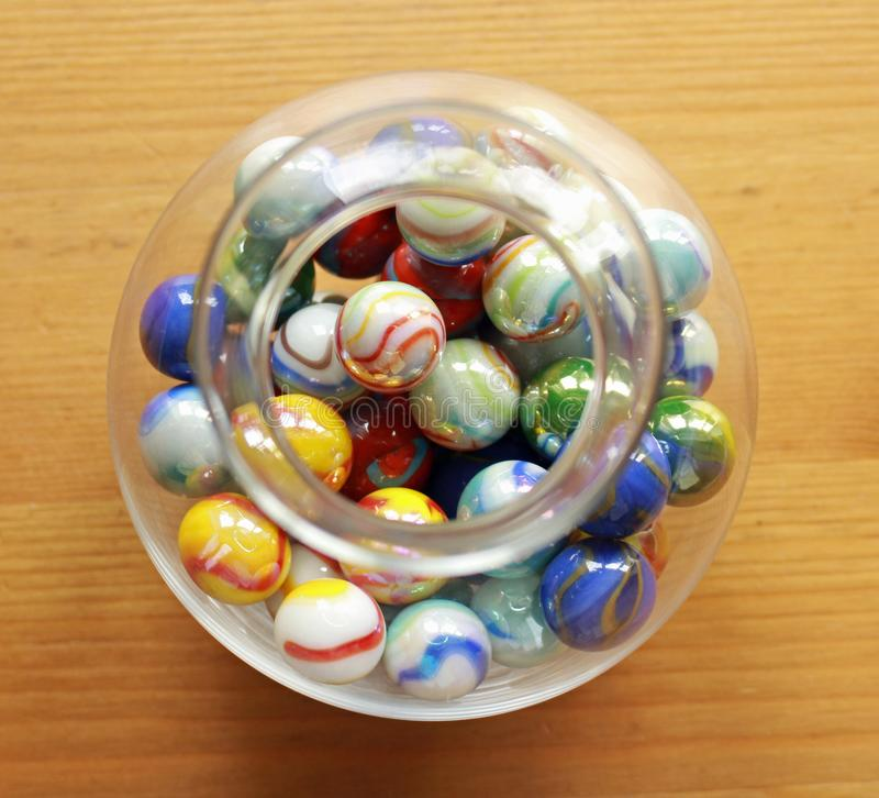 Colourful marbles in a round, glass jar viewed from above royalty free stock image