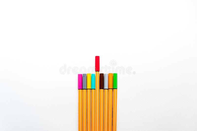 Colourful markers as a symbol of difference and creativity between individuals with one red marker marker higher than others stock photography