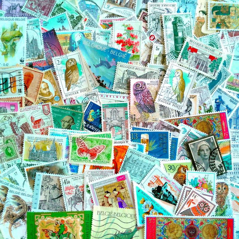 A colourful mix of mostly Belgian used postage stamps on various themes stock image