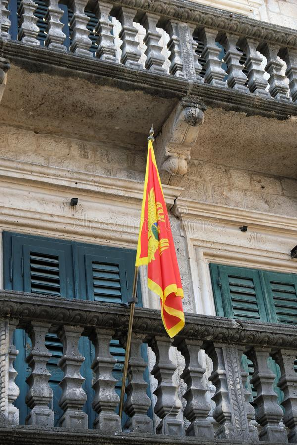 Montenegrin Flag Flying From Balcony, Kotor, Montenegro. Colourful Montenegrin flag flying from the balcony of an historic building in Kotor Old Town, Montenegro stock photos