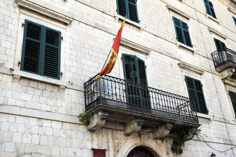 Montenegrin Flag Flying From Balcony, Kotor, Montenegro. Colourful Montenegrin flag flying from the balcony of a white stone formal building with green wooden royalty free stock images