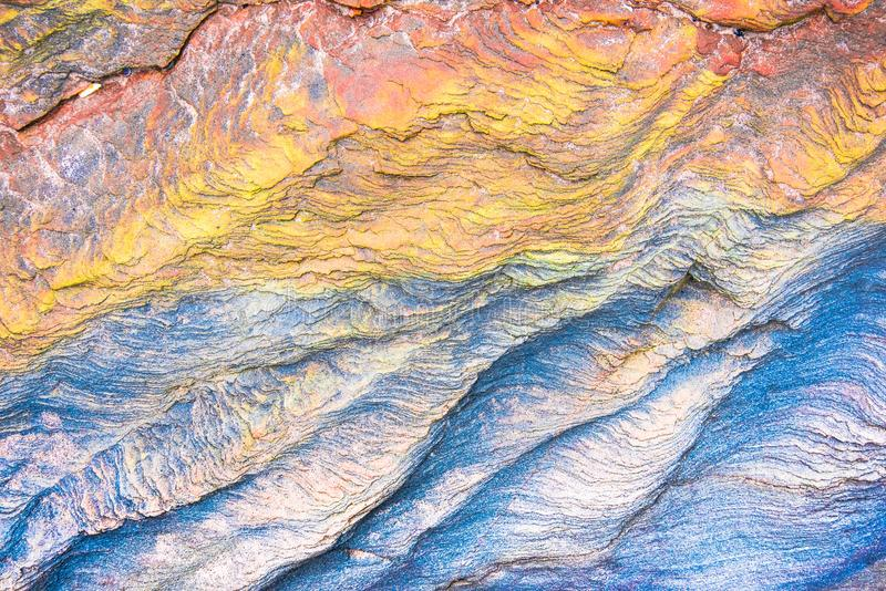 Colourful mosaics or rocks - layered sedimentary minerals. Exposed by sea - textured background stock image