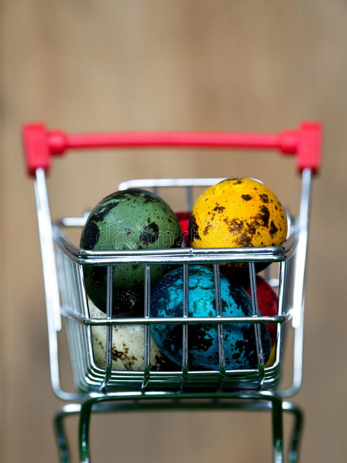 Colourful of multi easter eggs in red shopping cart on green grass the background is wooden board stock photography
