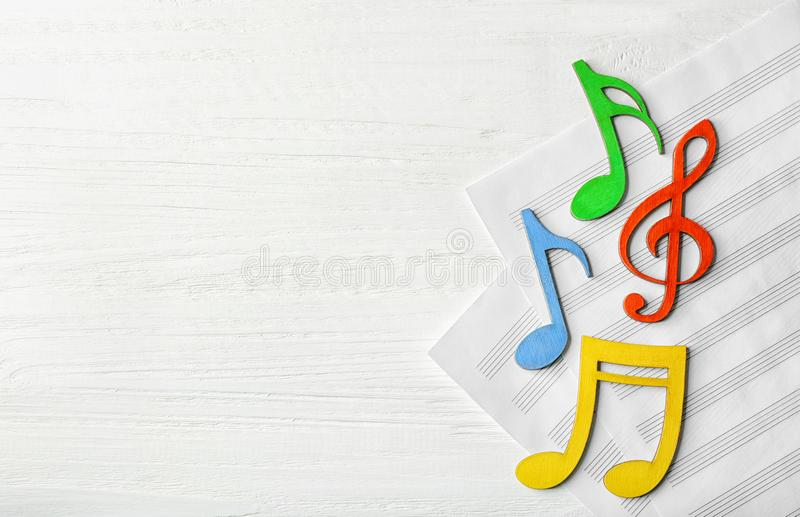 Colourful musical notes lying on music sheets. On white wooden background stock photos