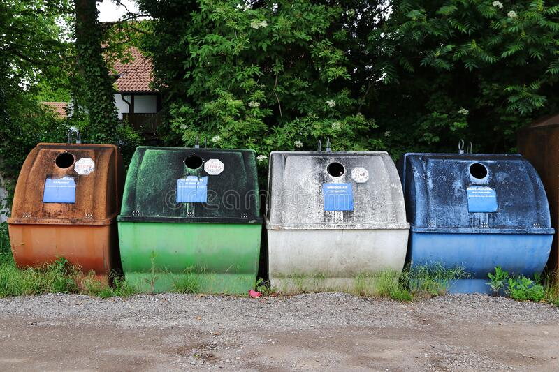 Colourful old waste containers for different coloured glass and tin cans royalty free stock photography